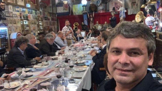 Lindbergh Farias posa para foto em mesa com outras pessoas, dentro de restaurante na Argentina