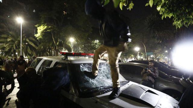 Homem depreda carro da polícia durante protesto