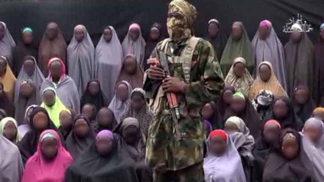 Dans la vidéo, un homme masqué se tient debout devant un groupe de jeunes filles.