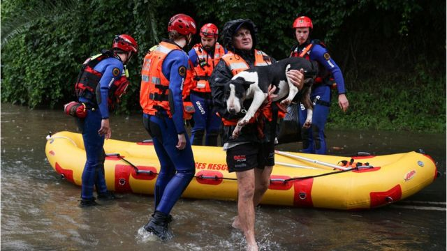 A local resident and his dog are brought to safety by a State Emergency Service rescue team in the midst of widespread flooding and severe weather across the state of New South Wales, in Sydney, Australia, March 21, 2021