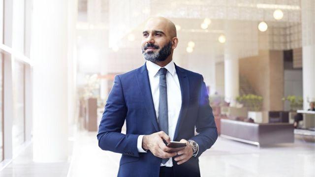 Hombre observa hacia el horizonte con el celular en la mano.