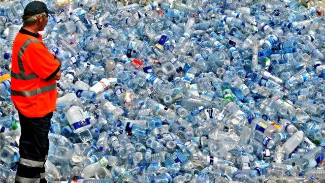 Homem olhando pilha de garrafas plásticas