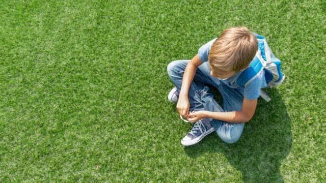 Criança sentada na grama