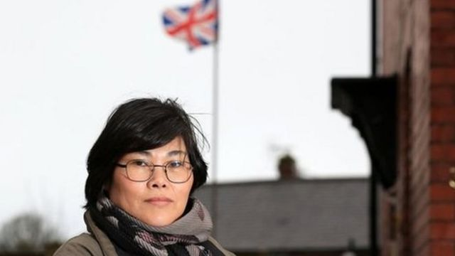 Jihyun Park berdiri di depan sebuah rumah dengan bendera Britania Raya berkibar di belakang