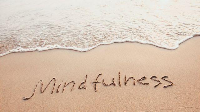"""Playa con la palabra """"mindfulness"""" escrita en la arena"""