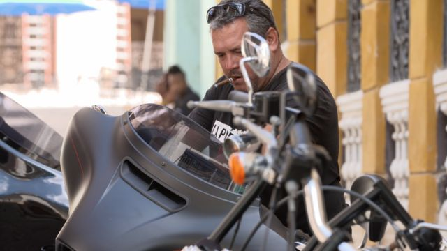 Ernesto Guevera with a cigar on a motorbike in Cuba