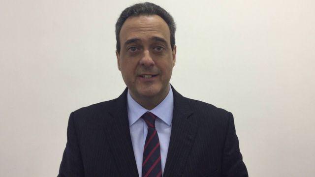 Roberto Barbosa Alves fala no vídeo, em frente ao muro