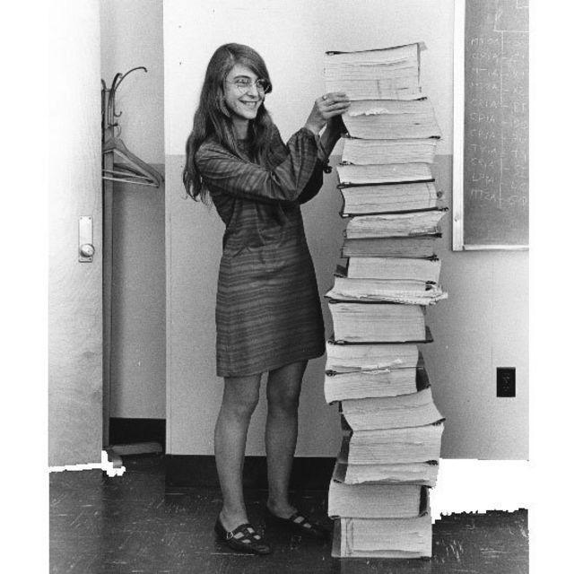 Margaret Hamilton junto a una pila de libros con programas de software escritos para la misión Apolo