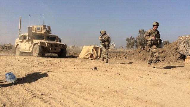 Two US soldiers are seen near a military vehicle