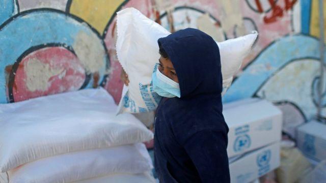 طفل فلسطيني يحمل كيس طحين من المساعدات في غزة