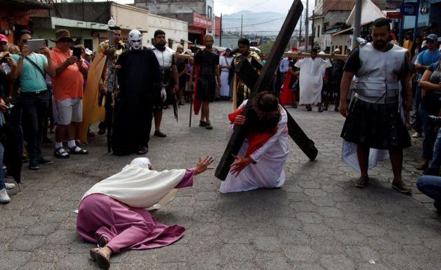 """Persona cargando una cruz representando la """"vía crucis""""."""