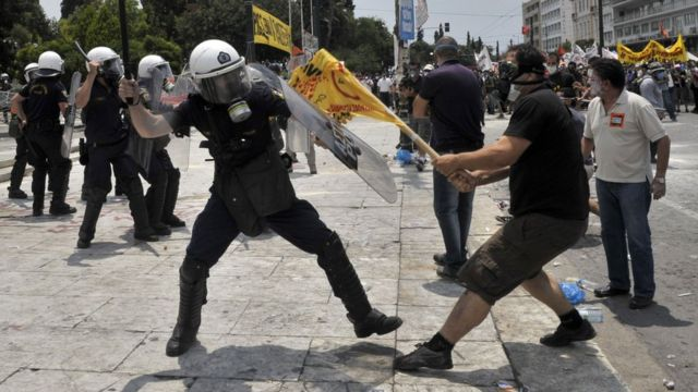 Demonstrators clash with riot police outside the Greek Parliament on June 29, 2011 in Athens