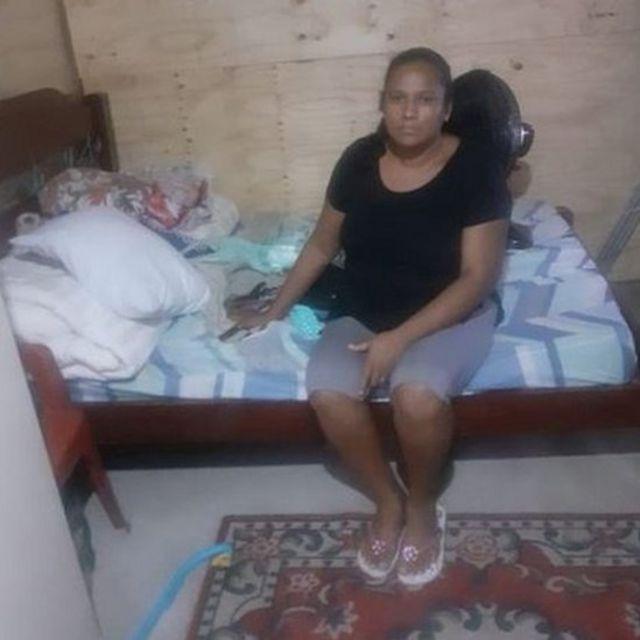 Valdirene sentada na cama