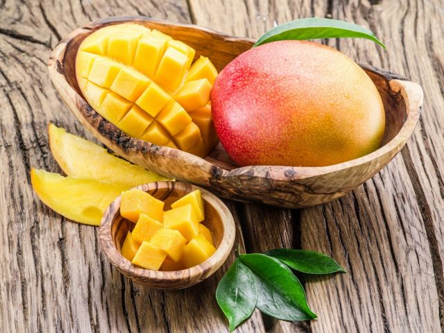 Wooden bowl with half a chopped mango and one whole mango