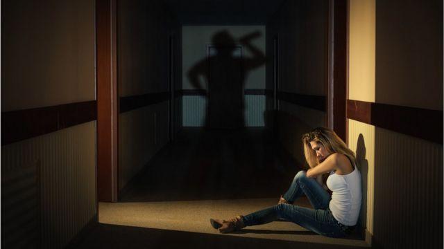Adolescente sentada em corredor