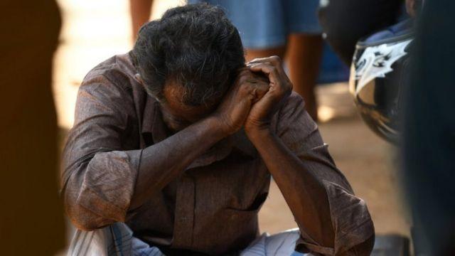 श्रीलंका में अस्पताल के बाहर बैठा एक व्यक्ति