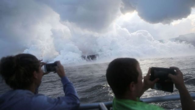People take photos on a tour boat as steam plumes rise while lava enters the Pacific Ocean, after flowing to the water from a Kilauea volcano fissure, on Hawaii's Big Island on May 20, 2018 near Pahoa, Hawaii.