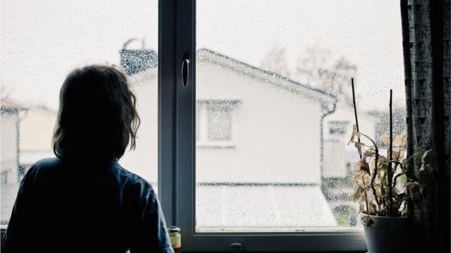Persona de espaldas asomada a la ventana