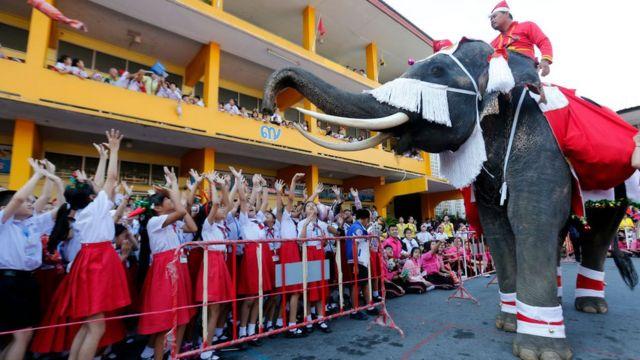 Des enfants très heureux de voir le Père Noël sur un éléphant en Thaïlande.