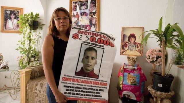 Marisela Escobedo sosteniendo un cartel con la foto del asesino de su hija.