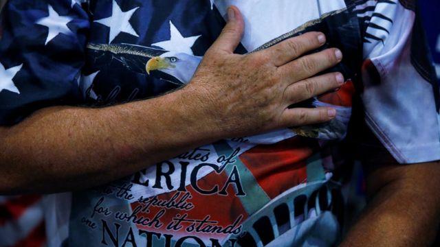 Seguidor de Trump con la mano en el corazón vistiendo una remera con la bandera de Estados Unidos y el águila.