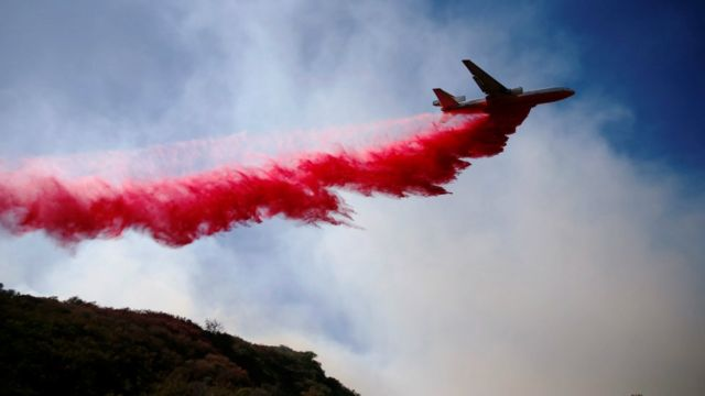 An aircraft drops flame retardant as firefighters battle the Woolsey Fire as it continues to burn in Malibu, California, U.S. November 11, 2018