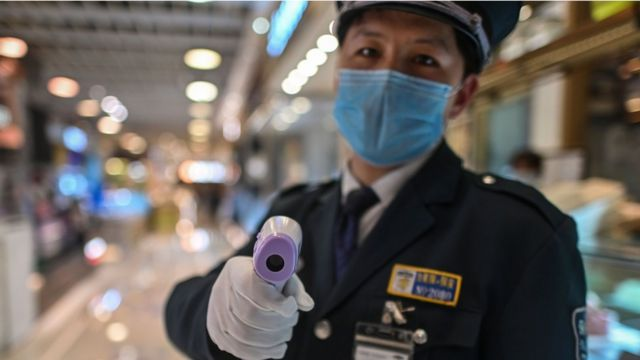 Security guard in China hold up an infrared thermometer