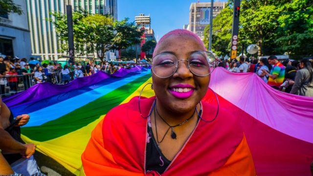 Mulher sorri com uma bandeira do arco-íris em uma marcha de orgulho gay