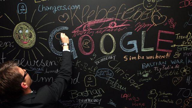"""Un hombre escribe en un pizarrón donde se lee la palabra """"Google"""", entre otras."""