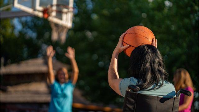Criança de costas, em cadeira de rodas, jogando basquete