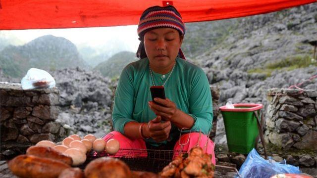 ผู้หญิงกลุ่มชาติพันธุ์ม้ง กำลังดูโทรศัพท์ที่แผงขายของของเธอที่ตลาด (ต.ค. 2018)