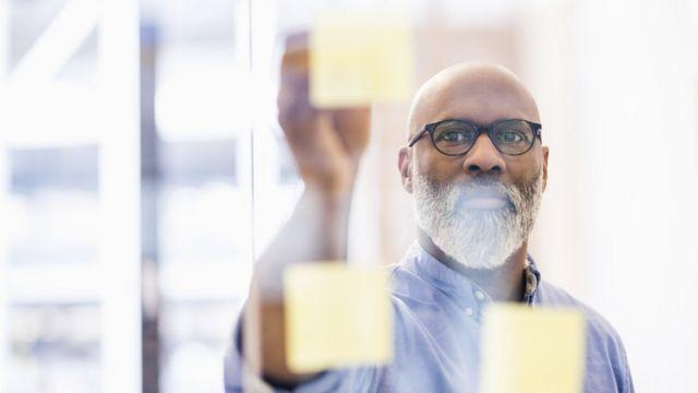 Hombre pegando papeles en un vidrio 8 conseils d'un expert qui vous aideront à oser changer de carrière (et comment votre âge l'influence) -  116489855 gettyimages 951525434 - 8 conseils d'un expert qui vous aideront à oser changer de carrière (et comment votre âge l'influence)