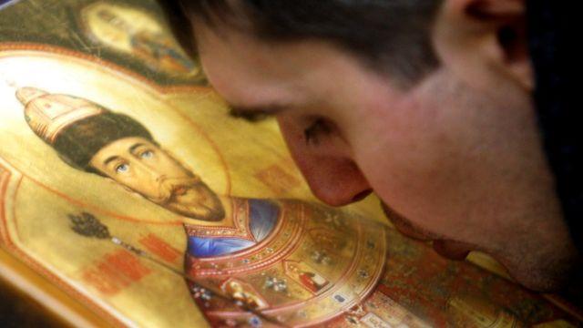 Un feligrés ruso besa el ícono de Nicolás II, febrero de 2011