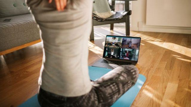Em primeiro plano, homem de camiseta cinza e calça listrada faz alongamento e parece interagir com uma tela de computador, onde outras quatro pessoas repetem seus movimentos