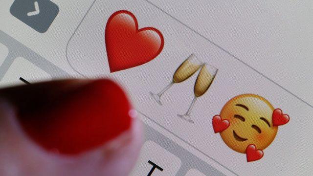 Dedo de mujer con emojis.