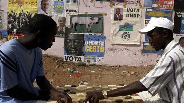 Des résidents de Bissau s'adonnent au jeu de dame devant un mur couvert d'affiches de partis politiques (illustration)