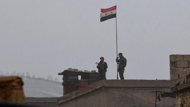 Şam ordusunun askerleri, SDG kontrolündeki Menbic'de bir binaya Suriye bayrağı çekerken görülüyor
