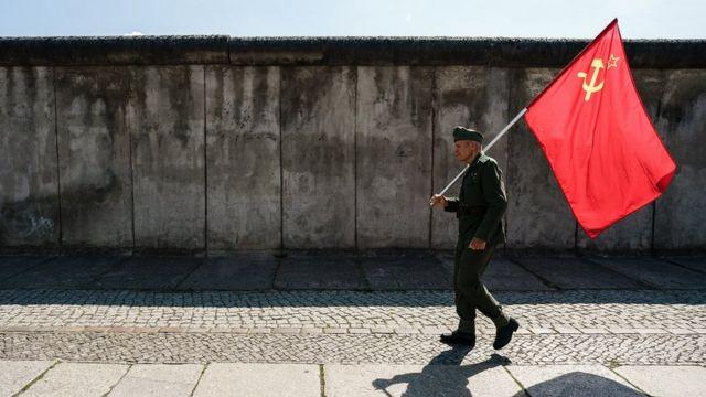 Человек с советским флагом у Берлинской стены