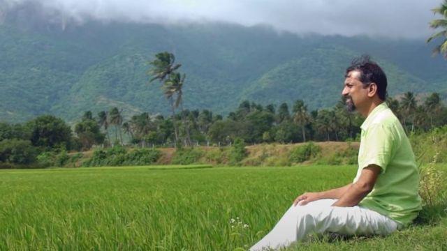 Sridhar sentado cerca de un cultivo de arroz