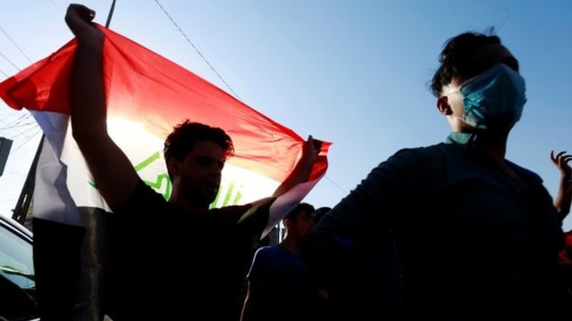 An Iraqi protester waves a flag in Basra