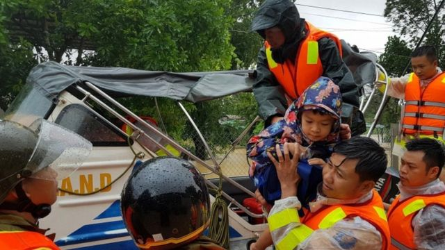 Municipal workers evacuate local people from flood water in Quang Tri province, Vietnam, o­n 18 October 2020