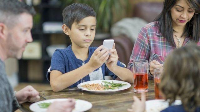 ينظر الطفل إلى هاتفه أثناء تناول الطعام
