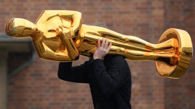 Man carrying giant Oscar statue
