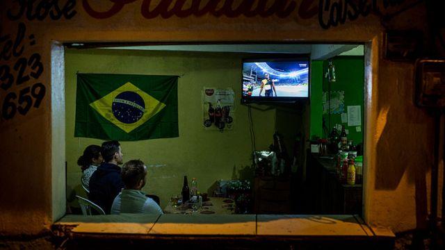 Люди смотрят Олимпиаду в баре в Рио-де-Жанейро