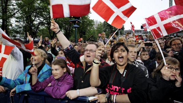 Personas con banderas de Dinamarca.