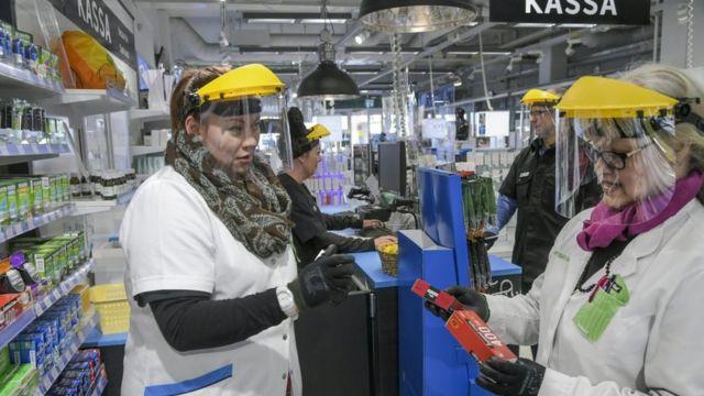 Empleadas de una farmacia en Finlandia con caretas, guantes y batas protectoras