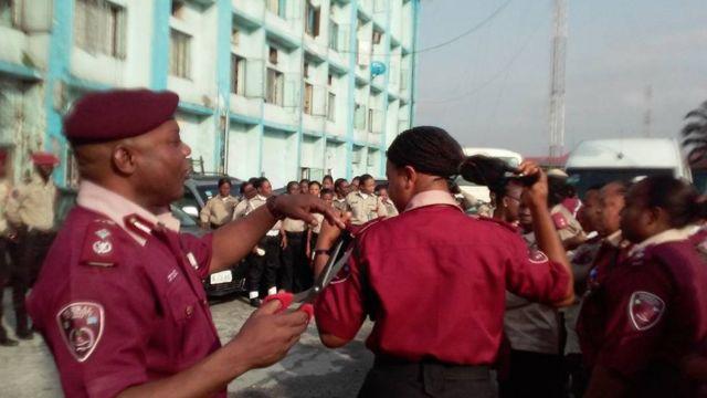 Man in maroon beret cuts a woman's hair in public
