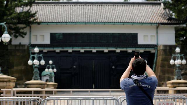 皇居で記念撮影する男性