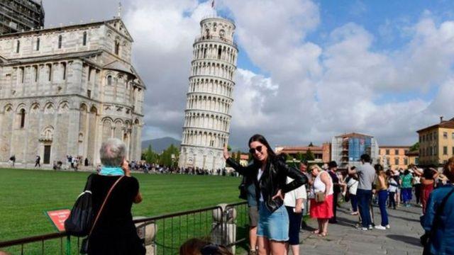 Mulher tirando foto com a torre de Pisa