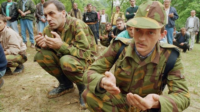 Muslim Bosnian soldiers praying during the funeral of three other soldiers.